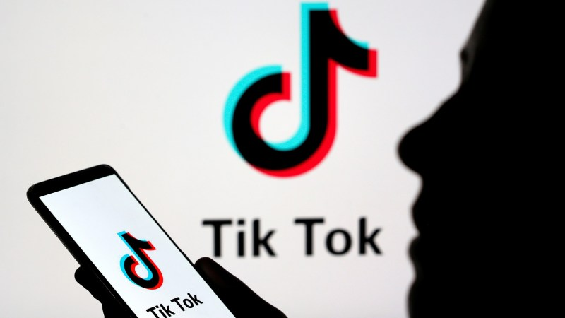 Person Holds A Smartphone With Tik Tok Logo Displayed In This Picture Illustration